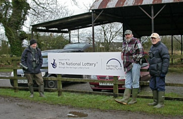Norman (Cumbria RSPB Coastal Reserves Manager) and birdwatchers admiring the sign pronouncing funding for new Reserve visitor facilities now in the process of being installed