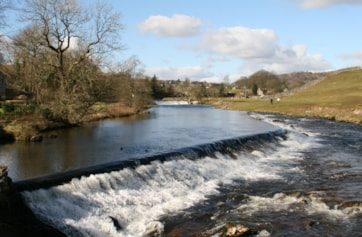 The weirs on the River Wharfe, as viewed from the Linton Falls footbridge. Looking back towards Grassington.
