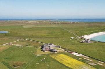 Aerial view of the island with the North Ronaldsay Bird Observatory and guest house in the foreground.