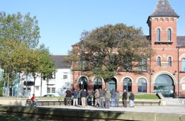 Birders watching a Western Bonelli's Warbler in the trees opposite Borough Hall.
