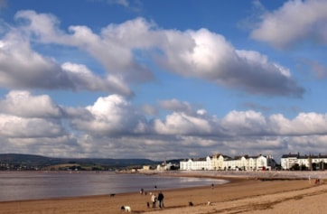 Exmouth beach and seafront, looking towards the Exe Estuary mouth with the Haldon Hills in the background.