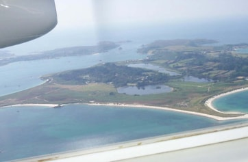 Aerial view from the Skybus Islander on departing St Mary's showing Tresco in foreground and Bryher more distant.