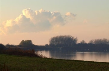 Looking west across the large lake at Welton Water with riverbank footpath on left.