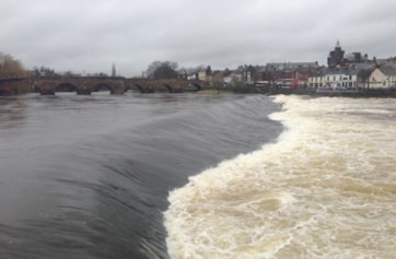 A view of the river Nith in spate at the weir on the Whitesands. Good for watching Goosanders fishing and Salmon leaping the weir. Devorgilla bridge is in the background.