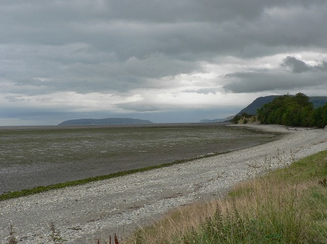 At low tide showing Puffin Island and Great Orme Head in the distance